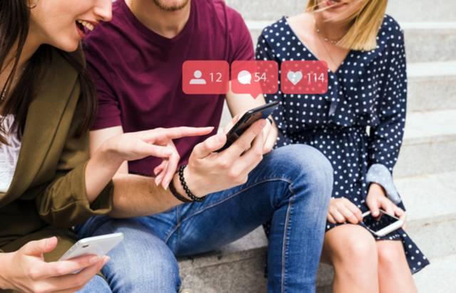Женщина указывает на человека, использующего значки уведомлений в социальной сети
