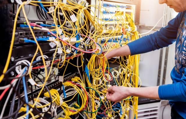 Сетевой инженер работает в серверной комнате – подключает сетевые кабели к коммутаторам