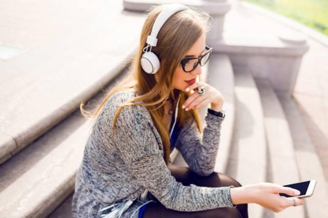 Молодая красивая девушка прослушивает музыку через наушники