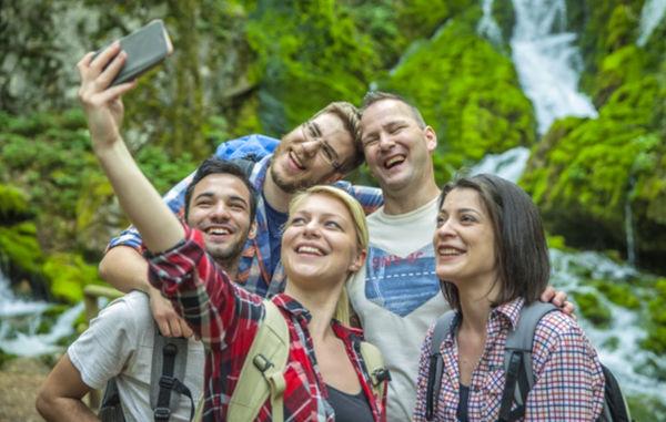 Группа молодых людей делает селфи-фотографию во время отдыха на природе