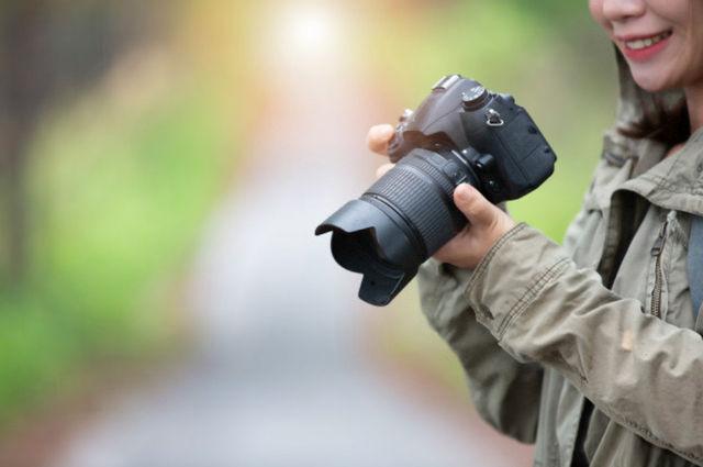 Девушка фотограф с фотоаппаратом в руках готовится сделать снимок