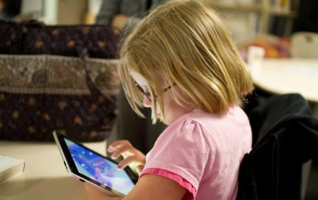 Девочка играется с планшетом на диване