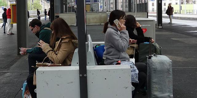 Люди на железнодорожной станции активно используют смартфоны