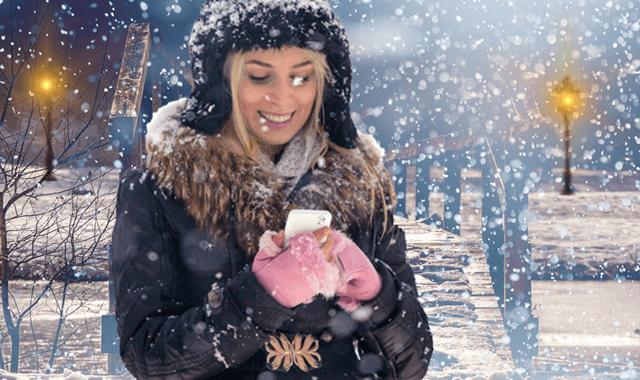 Использование смартфона в морозный день во время снегопада