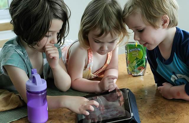 Маленькие дети изучают возможности планшета