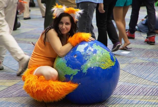 Девушка в костюме рыжей лисы обнимает земной шар