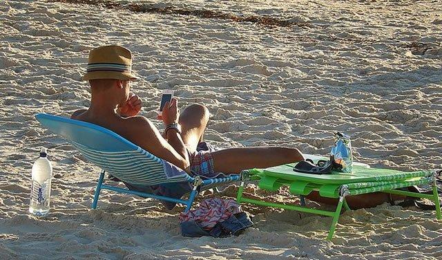 Мужчина отдыхает на пляже со смартфоном в руках