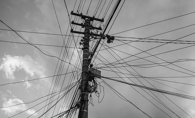 Столб опутанный множеством сетевых и телефонных кабелей