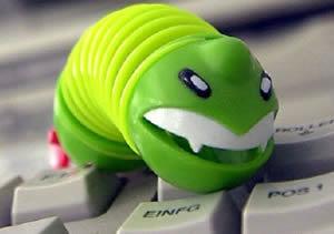 Зеленный игрушечный червь на клавиатуре