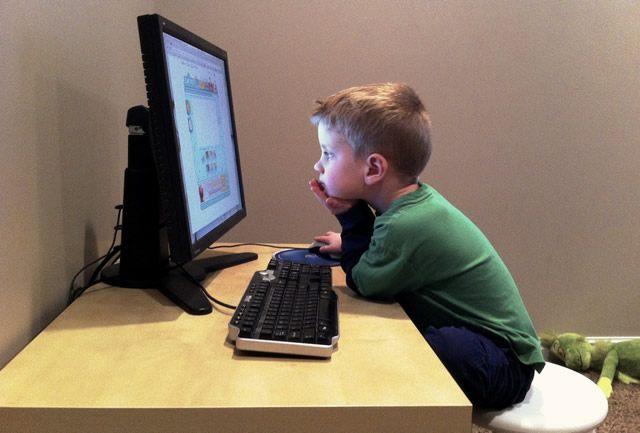 Мальчик за компьютером изучает сайты в Интернете