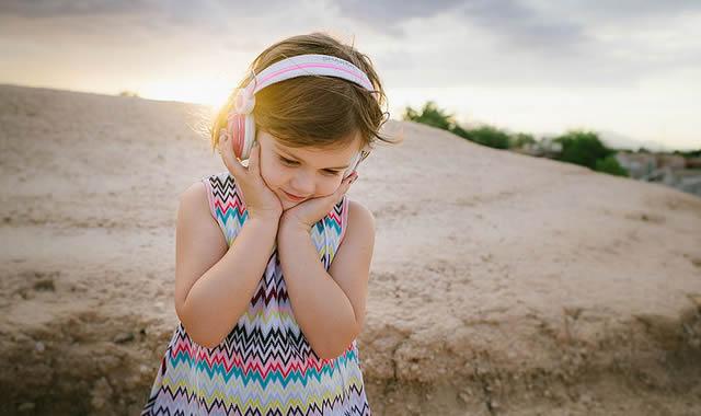 Маленькая девочка в бело-розовых наушниках слушает музыку