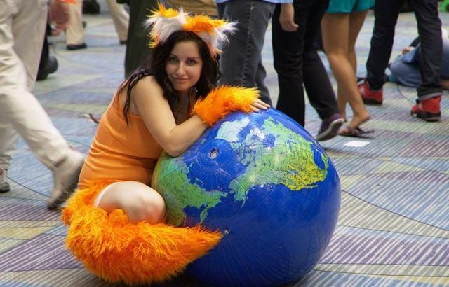 Девушка в костюме рыжей лисички обхватывает земной шар