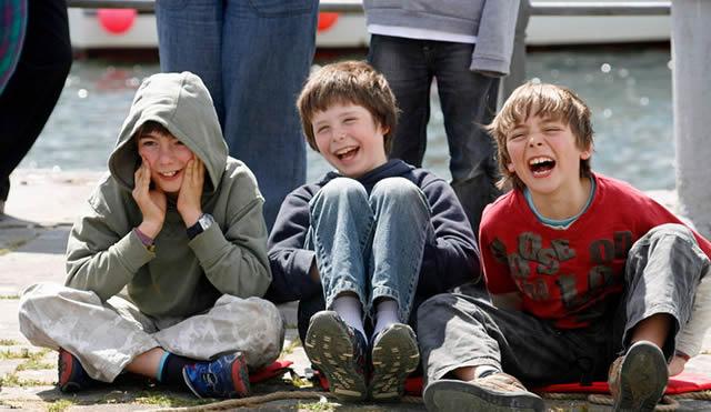 Дети смеются, сидя на тротуаре