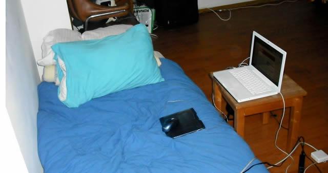 Ноутбук рядом с кроватью на табуретке