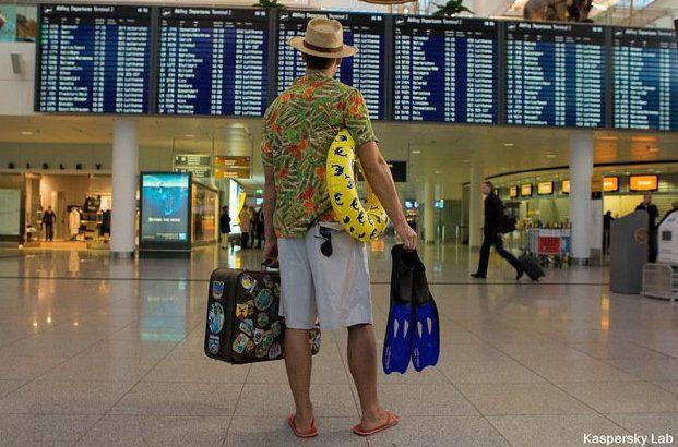 Мужчина в пляжной одежде и с багажом смотрит расписание отправления самолетов