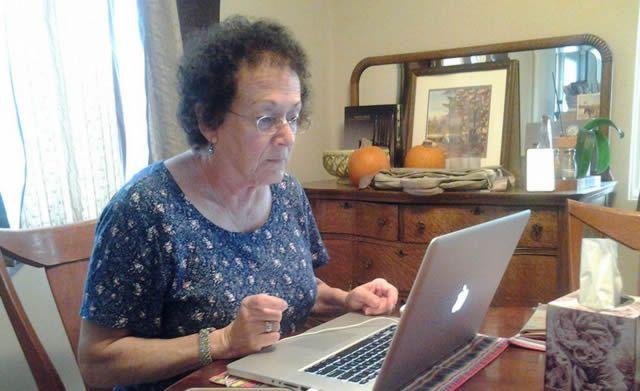 Пожилая женщина изучает просторы Интернета