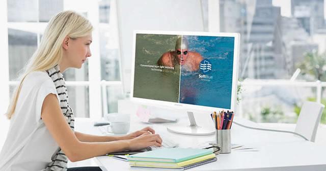 Девушка работает за монитором Philips с технологией SoftBlue, защищающей глаза