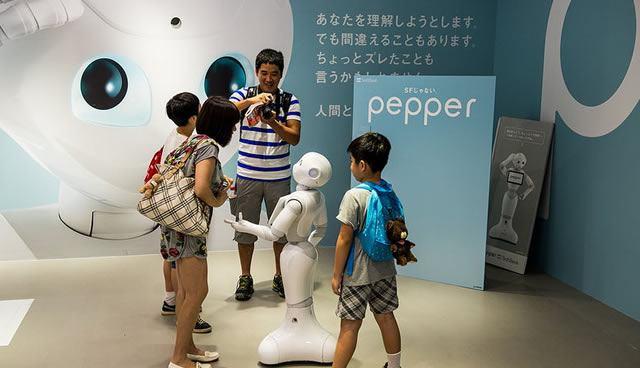 Человекоподобный робот Pepper ведет беседу с группой людей на презентации