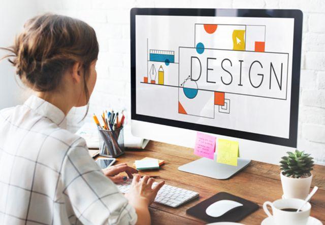 Дизайнер работает за столом перед монитором
