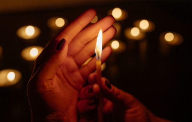 Зажжённая церковная свеча в руках скорбящего человека