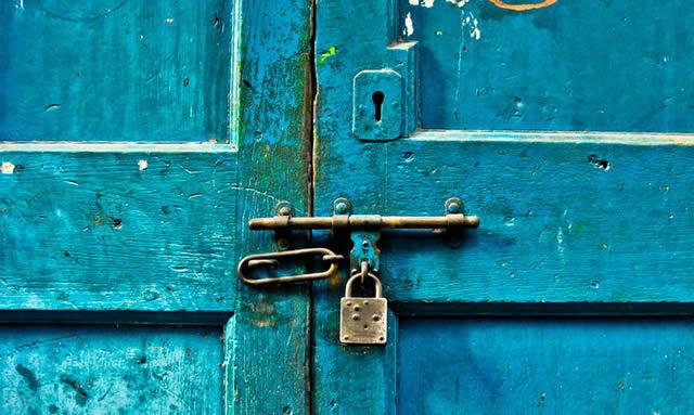Синяя дверь запертая на засов и замок